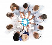 Directly above shot of medical team joining blue jigsaw pieces against white background poster