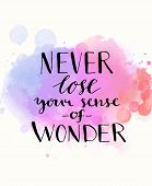 Never lose your sense of wonder. Black inspirational quote on purple watercolor imitation background, brush typography for poster, t-shirt or card. Vector calligraphy art poster