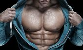 Strong Athletic Man showing six pack abs. closeup isolated over black background poster