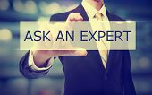 Business man holding Ask An Expert on blurred abstract background poster