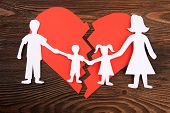 Paper cutout silhouette of a family split apart on a paper heart, divorce concept poster