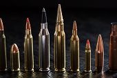 Number of large-caliber ammunition of different caliber in one line on a dark textural wooden background. Studio shot. poster