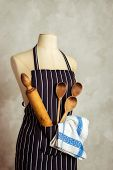Apron on mannequin with baking utensils and cloth in pocket poster