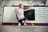 accident prevention. The child unattended playing in the kitchen with a gas stove. without retouch poster