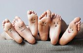 Human soles with painted faces close-up. Concept of feet care. poster
