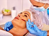Woman middle-aged in spa salon with beautician. Female giving lips botox injections. poster