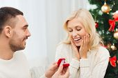 love, christmas, couple, proposal and people concept - happy man giving diamond engagement ring in little red box to woman at home poster