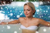 people, beauty, spa, healthy lifestyle and relaxation concept - beautiful young woman wearing bikini swimsuit sitting in  at poolside with snow effect poster