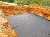 Membrane laid to separate the sand from the gravel in the construction of a sand and gravel filter bed poster