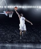 Athletic African American Basketball Player scoring a layup basket during a professional basketball game in a crowded arena poster