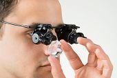 Closeup of jeweler examining diamond with magnifying glass against white background poster