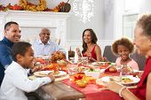 Family With Grandparents Enjoying Thanksgiving Meal At Table poster