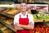 Portrait of smiling man wearing apron at supermarket poster