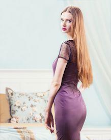 Woman In Purple Dress In Luxury Bedroom Interior