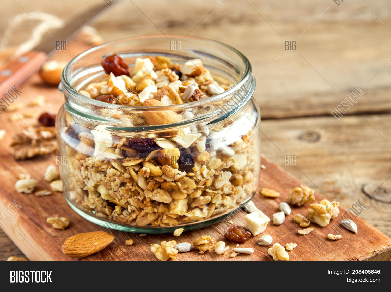 Homemade granola with nuts and seeds in glass jar for healthy breakfast - organic healthy vegan vegetarian diet detox recipe food granola musli.