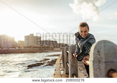 Smiling Woman Stretching On Railing At Seaside Road