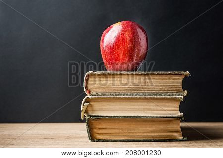 Stack Pile of Old Books Red Glossy Apple on Top. Learning Education Knowledge Concept. Blackboard Background. Classrom. Copy Space. Conceptual