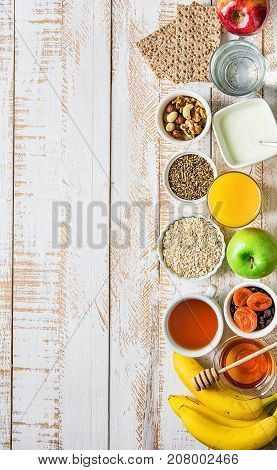 Healthy Food Fiber Source Breakfast Oatmeal Honey Fruits Apples Banana Orange Juice Water Green Tea Nuts. White Plank Wood Table. Rustic. Border Composition.Flat Lay Top View.