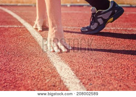 Runner in start position. Hands on starting line. Sport running in stadium.
