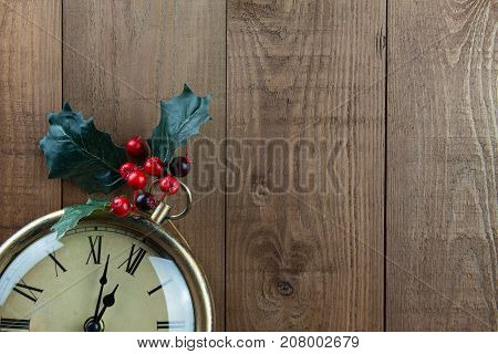Christmas vintage clock with Holly berries on a wood background. Part of clock showing. Time almost 12 o'clock almost Christmas! Vintage traditional warm brown colors with bright red berries. Lots of copy space.