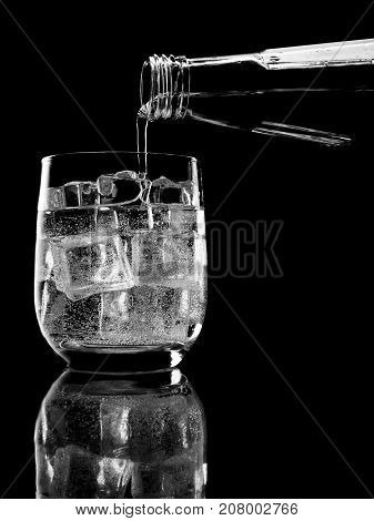 Bottle of soda mineral water pouring into glass on black background.  Carbonated purified water. Contour with gradient and highlights