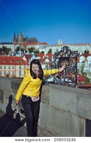 Prague Czech Republic-October 9 2017: The tourist touches the Relief of Jan Nepomuk's overthrow of the Vltava River at the Charles Bridge in Prague