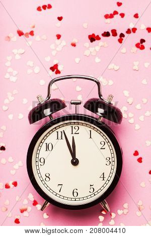 Alarm clock on a pink background with small hearts. The concept of the time of love, the time of date, the wedding, the day of St. Valentine, New Year