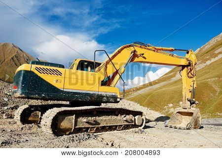 excavator loader machine at mountain road construction site
