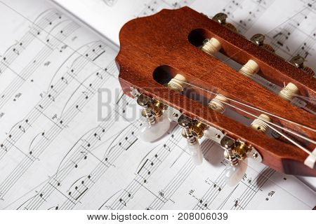 closeup of acoustic guitar on music notes