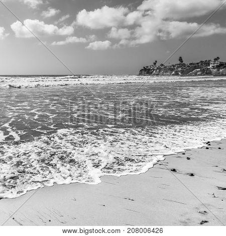 Ocean surf. Sea white foam on sand beach. California coast near San Diego. Black and White