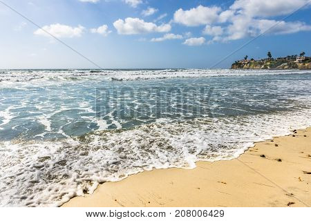 Ocean surf. Sea white foam on sand beach. California coast near San Diego.