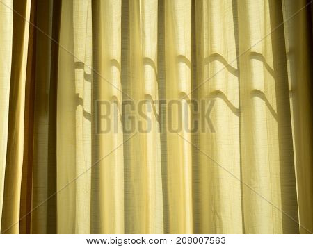 Soft yellow linen texture blinds curtains with sunlight through the windows. sun-blind.