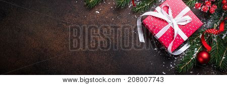 Christmas background or greeting card. Christmas red present box fir tree and decorations on dark stone table. Top view. Long banner format.