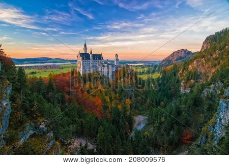 Amazing view on Neuschwanstein Castle with picturesque sky and colorful trees at autumn evening Bavaria Germany