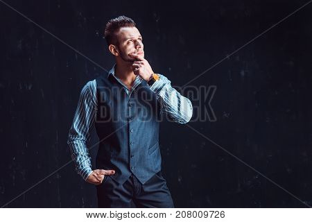 Portrait of sexy macho over dark background wearing a chronograph wrist watch. Masculine man in stylish clothes standing and thinking, hand on chin, looking up thoughtfully.