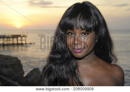 young attractive and glamorous African American black woman in chic and elegant summer dress posing relaxed on summer sunset beach in holiday vacation and beauty lifestyle concept