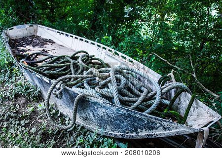 An abandoned dry boat with ropes on the shore.