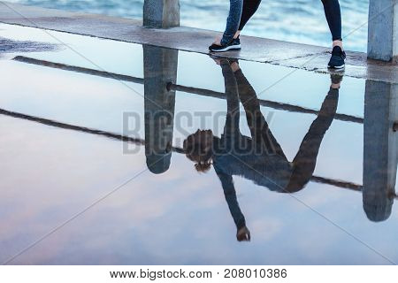 Exercising Woman Reflection In Puddle Of Water