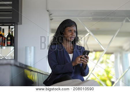 young attractive and happy black african american woman working from restaurant bar texting on internet mobile phone making business in entrepreneur networking and success concept