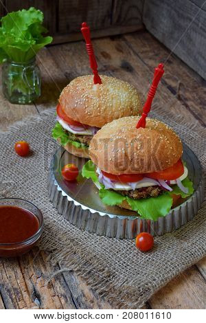Veggie Burgers With A Chop Of Eggplant, Lettuce, Pickled Onions, Tomato On A Brown Wooden Background
