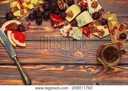 Cheese And Fruits Meal On Wooden Background