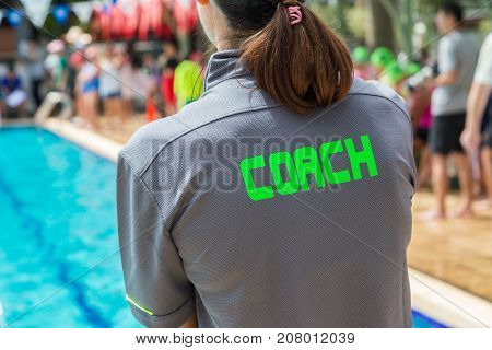 back of a swim coach's grey shirt with the green word Coach written on it; compose to leave space on left side for text or graphics; good background for sport or coaching theme