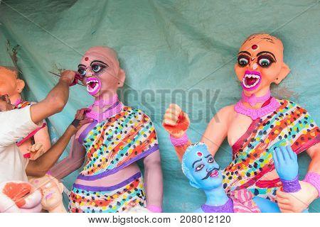 Artist preparing clay idols of female demons to be used during Kali Puja worshipping of Goddess Kali at Kumartuli - Kolkata India. Hindu festival of Deepavali or Diwali.