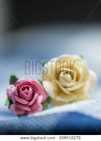 Select focus at pink artificial flowers. pink and yellow artificial flowers made of paper and placed on blue cloth stripes. Green artificial leaves are around artificial flowers.