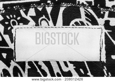Blank white textile clothes label on black and white background