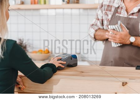 woman paying with pos terminal at cafe with bartender waiting over counter
