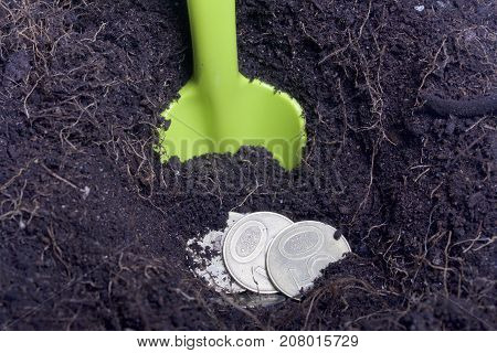 Money Buried In The Ground. The Pit Is Excavated, Coins Are In It. A Shovel Protrudes From The Groun