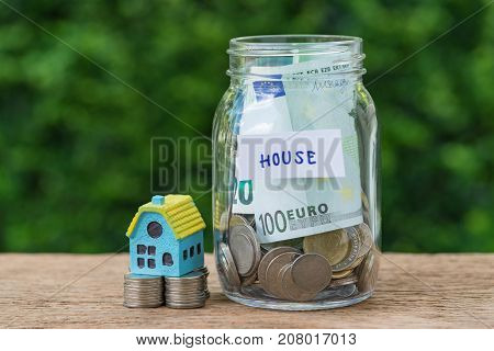 glass jar bottle labeled as house with full of coins and miniature house on stack of coins as home property or mortgage investment concept.