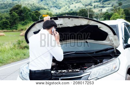 Man call for help on the phone.Are can not continue the way because of the broken car.