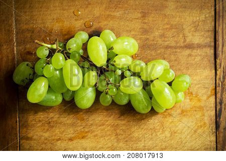 Sweet muscat grape with water drops on wooden table, top view